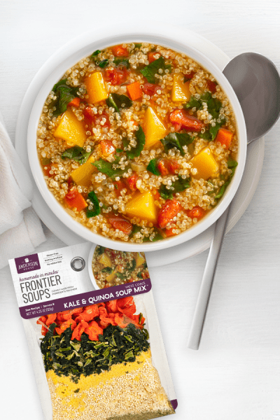West Coast Kale and Quinoa Soup in bowl with mix pack, spoon and napkin