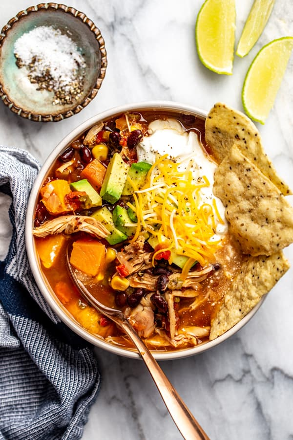 Chicken Tortilla Soup in bowl with spoon and special toppings