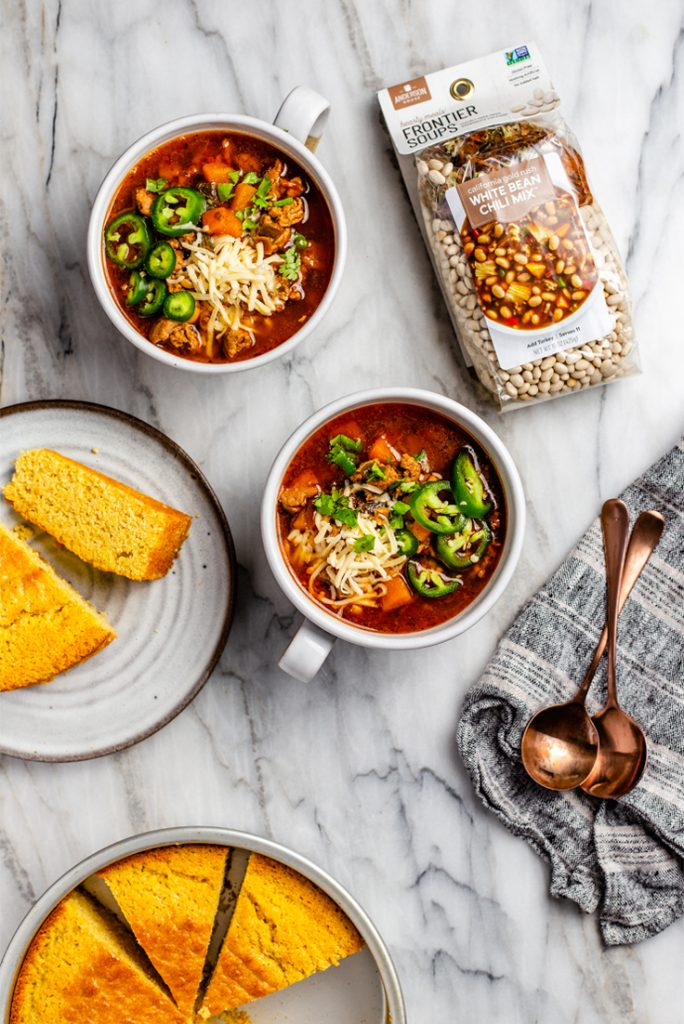 White Bean Chili in bowls with cornbread and soup mix